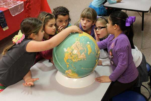Young students gathered around globe