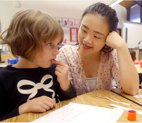 Lucy Lin speaking Mandarin with a kindergarten student.