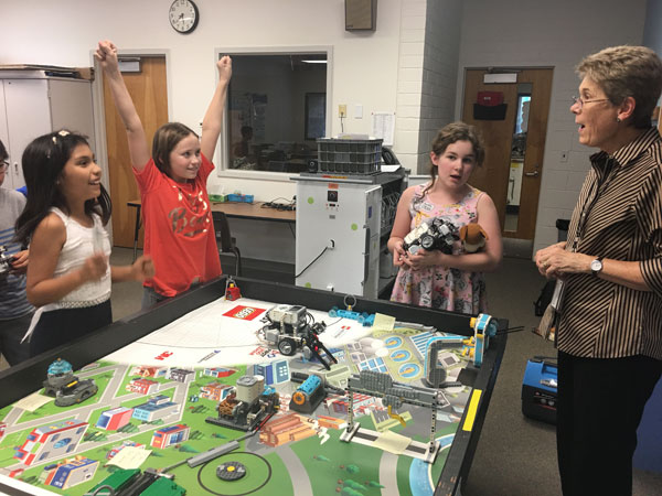 Three Robotics students with teacher
