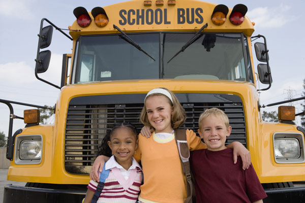 Three students in front of school bus