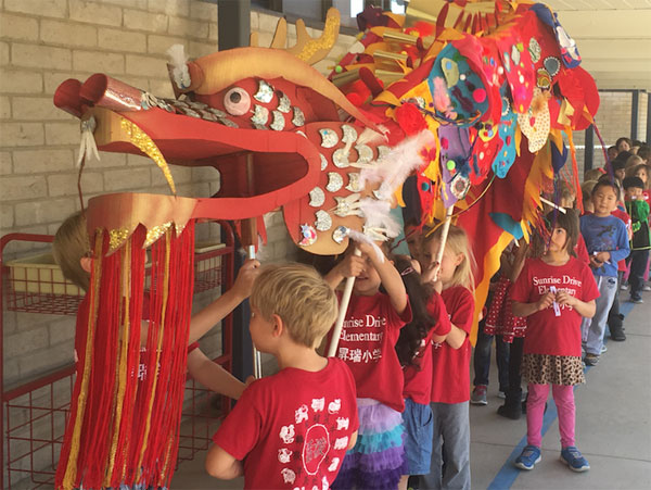 Kindergarteners holding a red paper dragon for the spring festival
